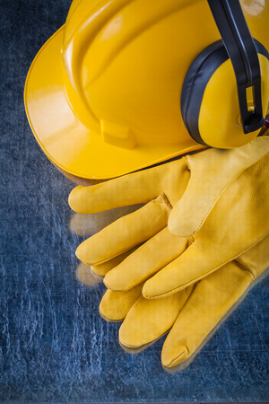 Earmuffs: Hard hat safety earmuffs and yellow leather protective gloves on metallic background construction concept.