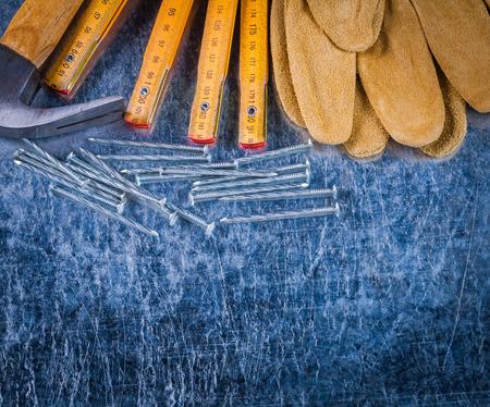 metro medir: Cierre de vista de protección guantes de trabajo clavos de medición del medidor de madera y martillo de orejas en concepto de edificio fondo metálico rayado.
