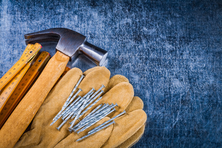 construction nails: Leather protective working gloves construction nails wooden meter and claw hammer on scratched metallic surface building concept. Stock Photo