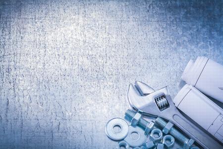 tuercas y tornillos: Arandelas de los pernos llave ajustable pernos tuercas y enrollados planos de construcci�n en el fondo met�lico visi�n horizontal concepto de mantenimiento.