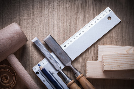 curled up: Wooden bricks hammer curled up planning chips firmer chisels square ruler pencil on wood board construction concept. Stock Photo