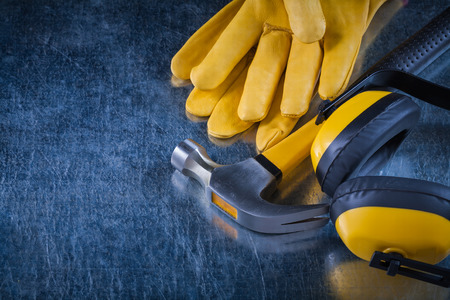 ear muffs: Noise insulation ear muffs claw hammer and leather construction gloves on metallic surface building concept.