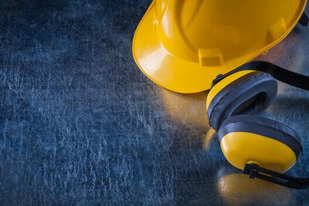 ear muffs: Noise insulation ear muffs and hard hat on scratched metallic background copy space image construction concept. Stock Photo