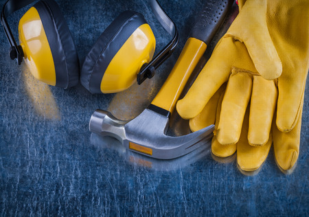 Earmuffs: Safety yellow earmuffs claw hammer and leather construction gloves on scratched metallic surface building concept. Stock Photo