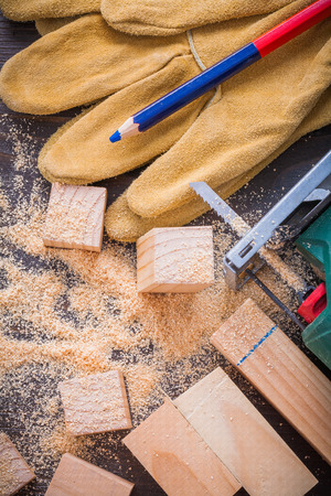 scobs: Pencil electrical fretsaw sawdust leather protective gloves and wooden bricks on vintage wood background construction concept.