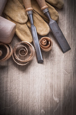 curled up: Wooden mallet curled up shavings flat chisels leather gloves on wood board vertical view construction concept. Stock Photo