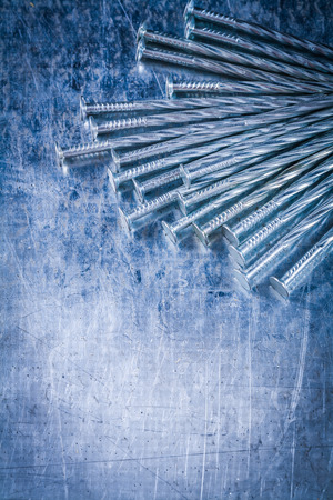 construction nails: Collection of stainless construction nails on scratched metallic surface building concept. Stock Photo