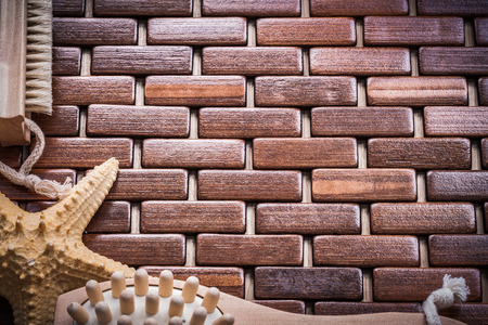 matting: Wood massager starfish and scrubbing brush on textured wooden matting sauna concept.