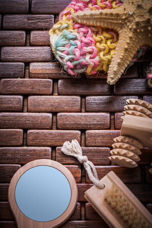 a bathing place: Handglass massager peeling brush and colorful bath sponge on textured wooden table mat sauna concept.