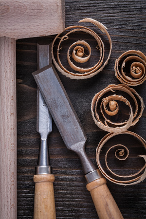 curled up: Wooden hammer firmer chisels and curled up shavings on vintage wood board construction concept.