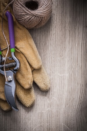 gardening gloves: Leather gardening gloves sharp metal secateurs and hank of twine on wooden background agriculture concept.