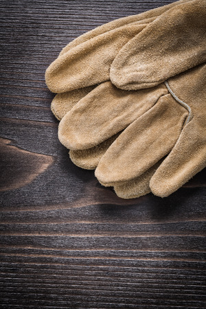 working gloves: Pair of leather working gloves on vintage wooden board close up view construction concept.