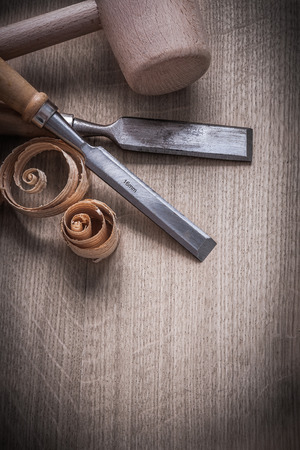 curled up: Wooden hammer curled up planning chips flat chisels on wood board construction concept.