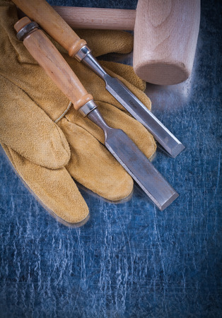 chisels: Wooden mallet firmer chisels and safety gloves on scratched metallic surface construction concept. Stock Photo