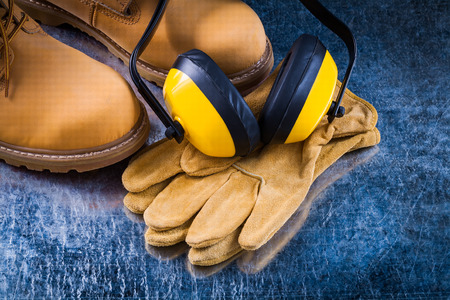 safety boots: Leather safety boots gloves and noise insulation ear muffs on scratched metallic background construction concept. Stock Photo