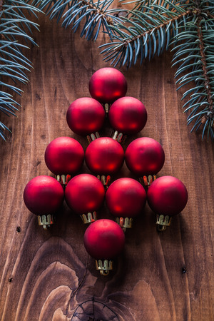firtree: red christmas baubles in the form of fir tree and branches firtree vintage wood board.