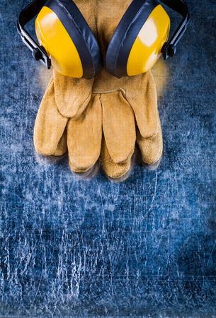 industrial noise: Leather safety gloves and noise insulation ear muffs on scratched metallic background copy space image construction concept.