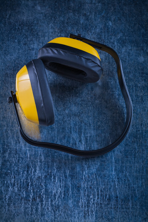 Earmuffs: Noise reduction over-the-ear earmuffs on metallic surface construction concept. Stock Photo