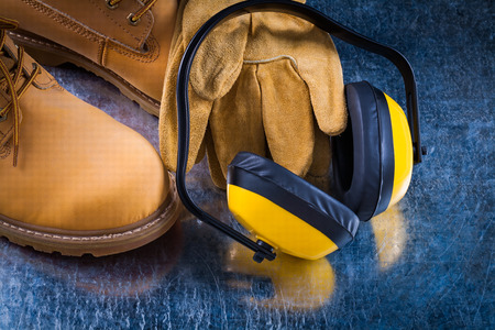 Earmuffs: Leather working lace boots protective gloves and earmuffs on scratched metallic background construction concept. Stock Photo