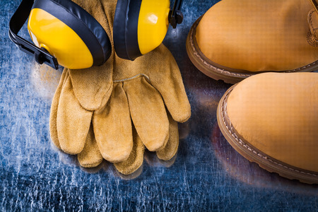 safety boots: Set of safety boots leather gloves and noise reduction headphones on scratched metallic surface construction concept. Stock Photo