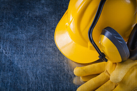 ear muffs: Hard hat ear muffs and leather protective gloves on scratched metallic surface construction concept.
