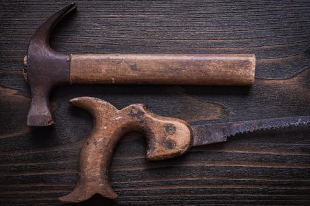 serrucho: Sierra de mano áspera Obsoleto y garra martillo sobre tabla de madera de la vendimia. Foto de archivo
