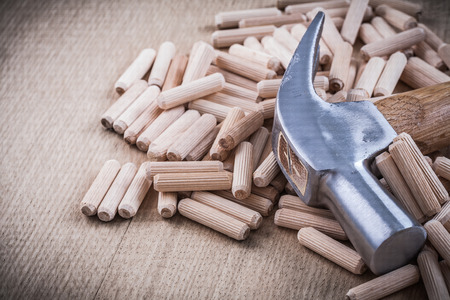 dowel: Dowel pins and claw hammer on wooden board construction concept.