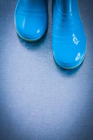 gum boots: Pair of waterproof rubber garden boots on metallic background.
