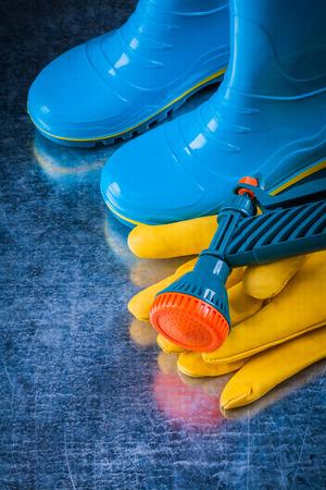 gumboots: Waterproof gumboots leather protective gloves and garden pistol. Stock Photo
