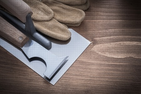 patching: Putty knife plastering trowel and leather safety gloves construction concept. Stock Photo