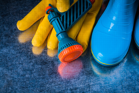 rubber boots: Composition of rubber boots leather safety gloves and water sprayer.