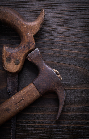 handsaw: Set of rusted handsaw and claw hammer on wooden board.