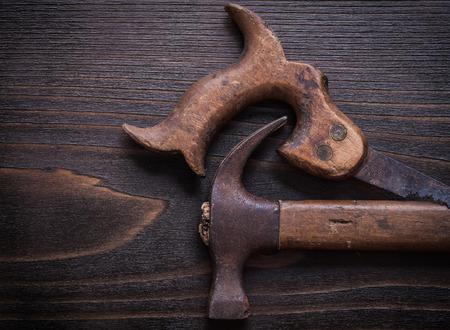 serrucho: Grunge sierra de mano larga y garra martillo sobre tabla de madera de la vendimia. Foto de archivo
