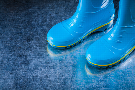gum boots: Pair of waterproof gum boots on scratched metallic surface.