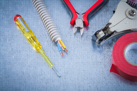 peeling rubber: Electrical tester screwdriver insulating tape wire protection cables nippers strippers. Stock Photo