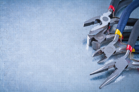 wire cutters: Insulated electric wire cutters on scratched metallic background construction concept.