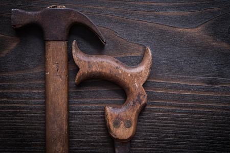 handsaw: Rusted messy handsaw and claw hammer on vintage wooden background.