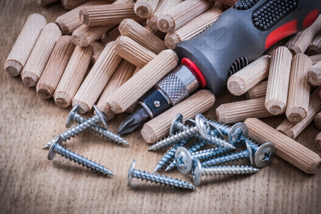 construction nails: Woodworking dowels stainless construction nails insulated turnscrew on wooden board.