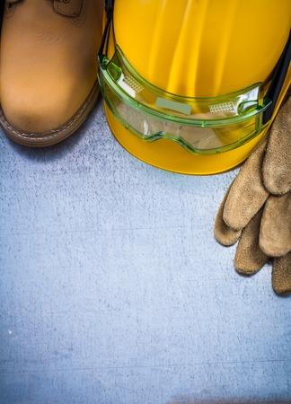 calzado de seguridad: Par de guantes de cuero zapatos de seguridad que construyen el casco y gafas de plástico transparentes sobre arañado la construcción del concepto del fondo metálico.