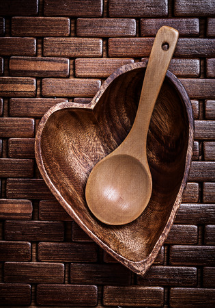 backcloth: Heartshaped wood bowl and spoon on wooden backcloth top view.