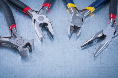 wire cutters: Set of electric metal wire cutters on scratched metallic background.