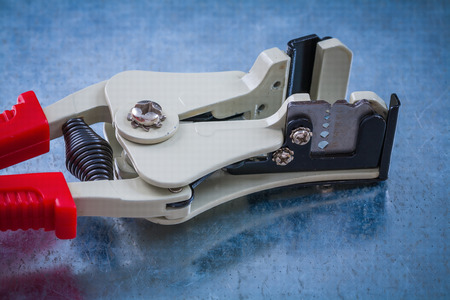 strippers: Automatic wire strippers on scratched metallic surface construction concept. Stock Photo