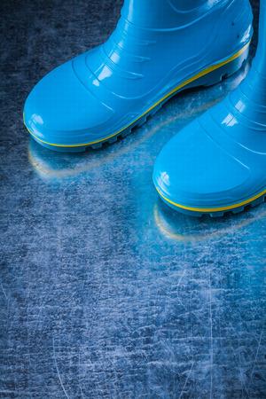 gum boots: Waterproof garden gum boots on scratched metallic surface.
