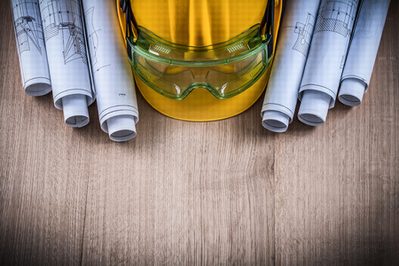 protective glasses: Protective glasses, construction plans and building helmet on wooden surface. Stock Photo