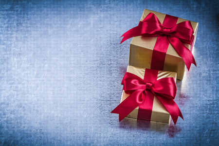boxed: Boxed golden presents with red bow on scratched metallic background. Foto de archivo