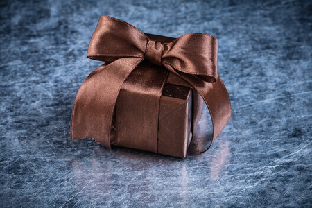 boxed: Boxed gift with tied bow on metallic background