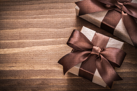 Present containers with brown ribbons on vintage wooden board. Stock Photo