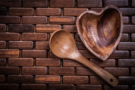 backcloth: Set of heartshaped wood bowl and spoon on wooden backcloth. Stock Photo