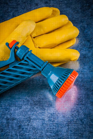 gardening gloves: Leather gardening gloves and water sprayer on scratched metallic background. Stock Photo