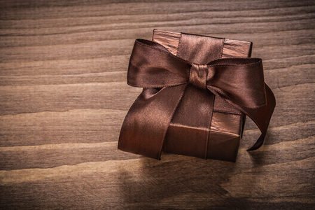 boxed: Boxed glittery gift container on vintage wooden board. Foto de archivo